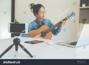 stock-photo-young-female-blogger-with-smartphone-recording-video-at-home-beauty-and-technology-concept-702586036