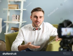 stock-photo-young-male-blogger-recording-video-at-home-410663020